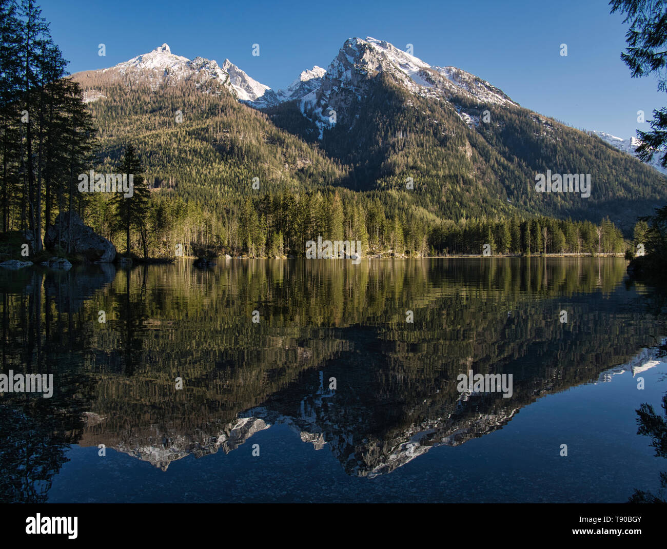 The still snow-covered mountains are reflected in the crystal-clear Hintersee lake. - Stock Image