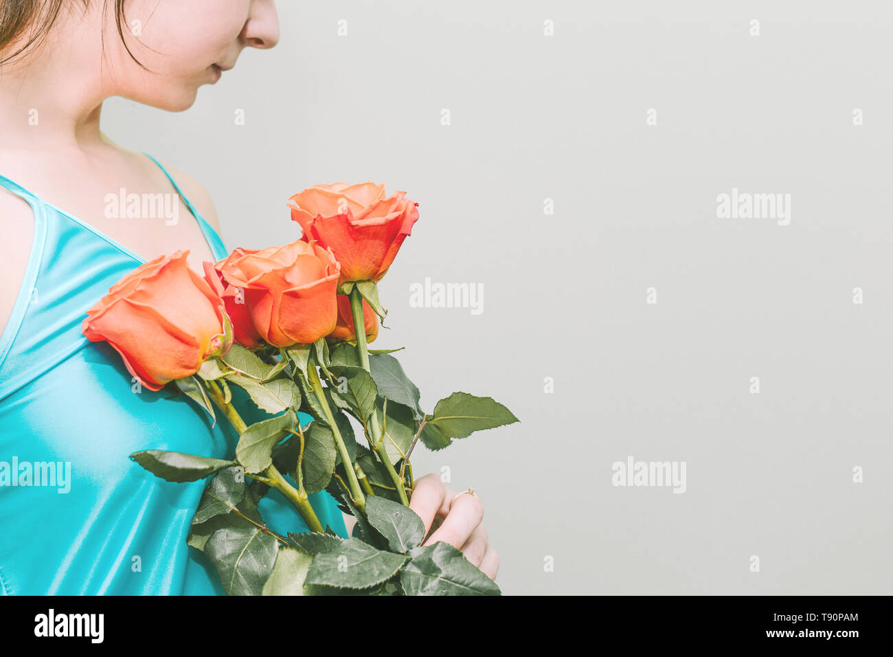 A young girl holds orange roses in her hands. A bouquet of bright flowers. On a beautiful girl wearing a turquoise shirt. Empty space for text - Stock Image