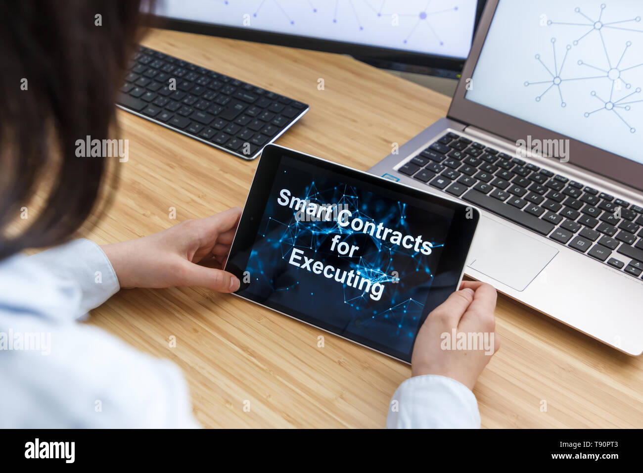 Business Female Using Smart Contracts For Executing. Illustration of Ethereum Blockchain on the Screen of Tablet, PC and Laptop. - Stock Image
