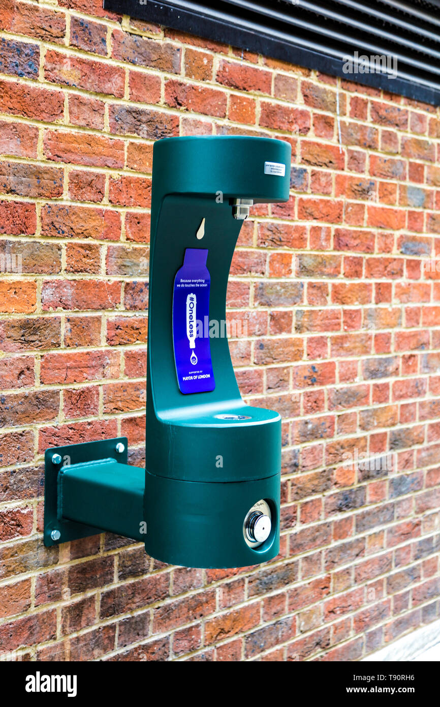 Water refill point installed onto a brick wall in central London, UK (St James's Market) - Stock Image