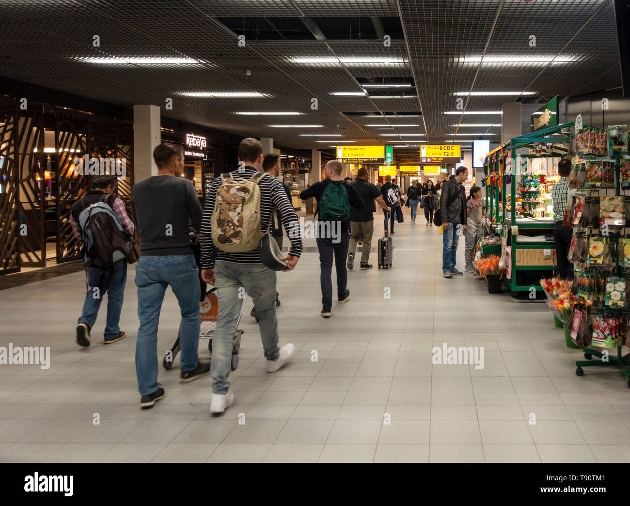 Air passengers walking between shops and restaurants through one of the main councourses of Schiphol Airport, Amsterdam - Stock Image