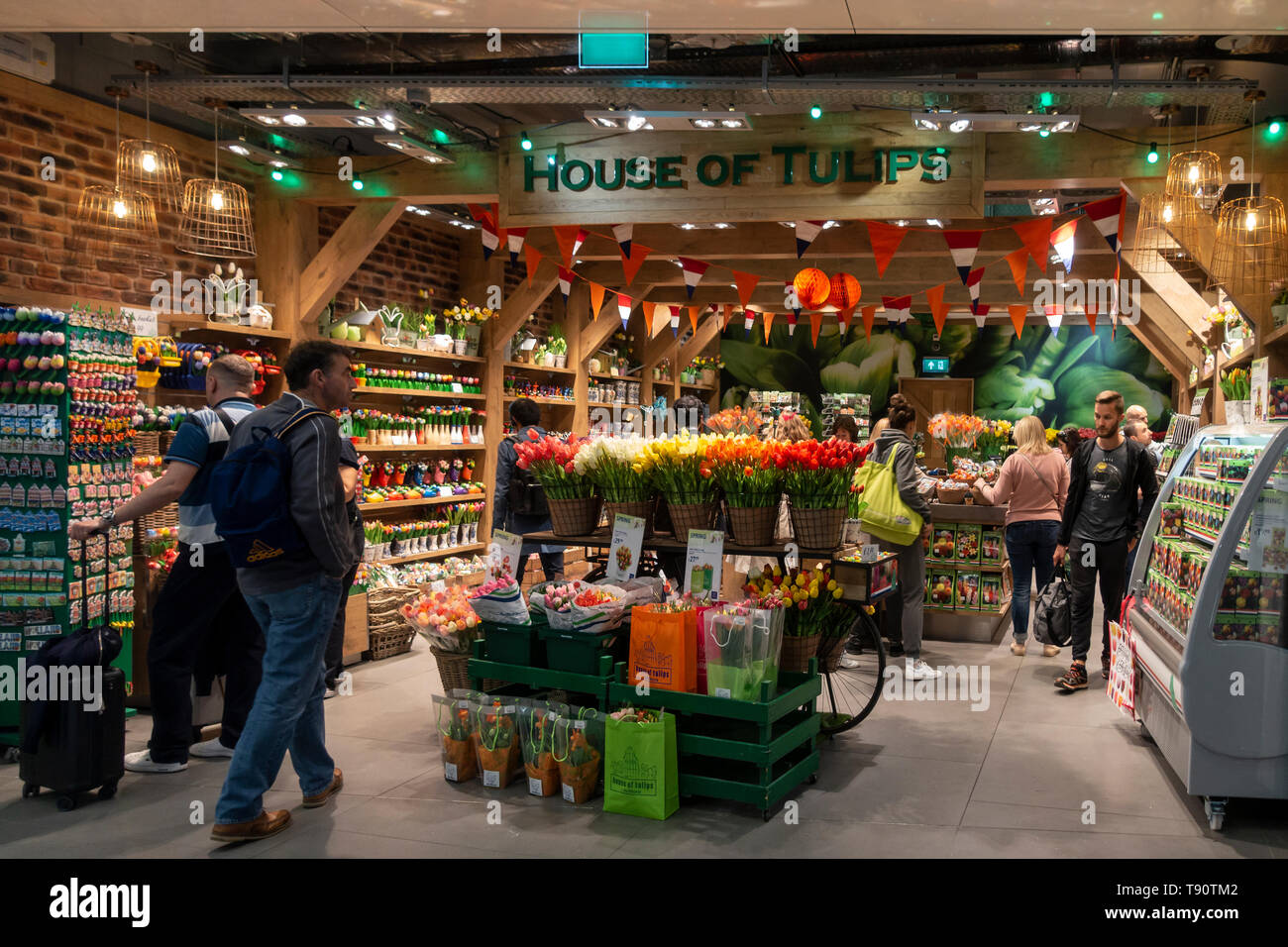 Air travellers browsing House of Tulips, a retail outlet with a Tulip theme, at Schiphol Airport, Amsterdam. - Stock Image
