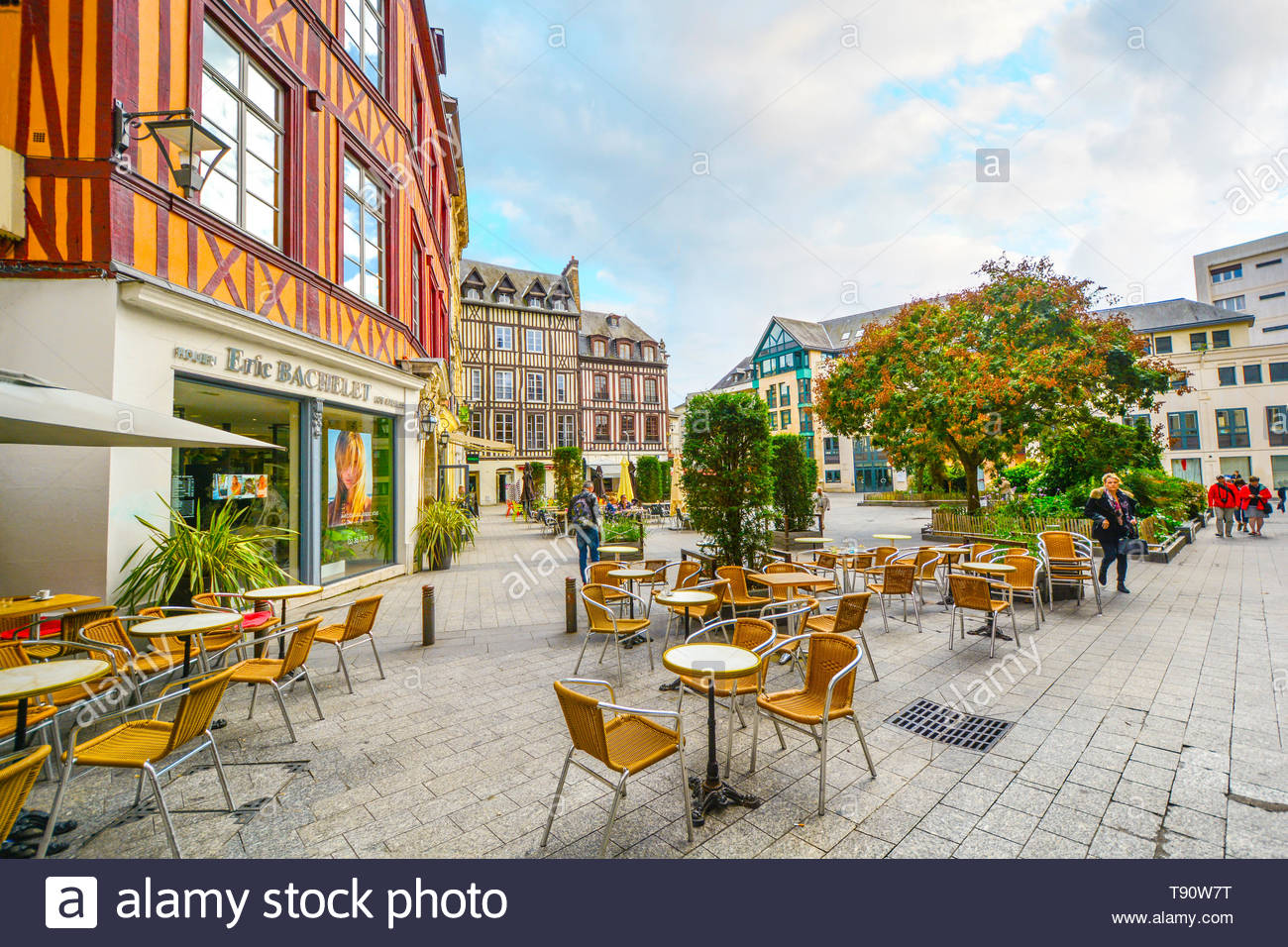 Timber frame homes line a town square in the medieval city of Rouen France with shops, a sidewalk cafe and tourists enjoying a sunny autumn day Stock Photo
