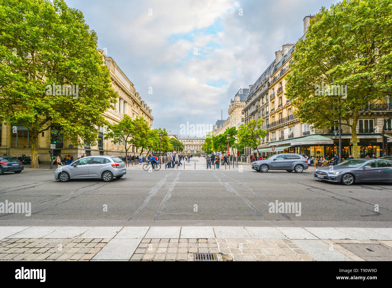 A street scene on the Ile de la Cite in the fourth arrondisement with the Palais du Justice visible on the right side of the pedestrian walkway Stock Photo