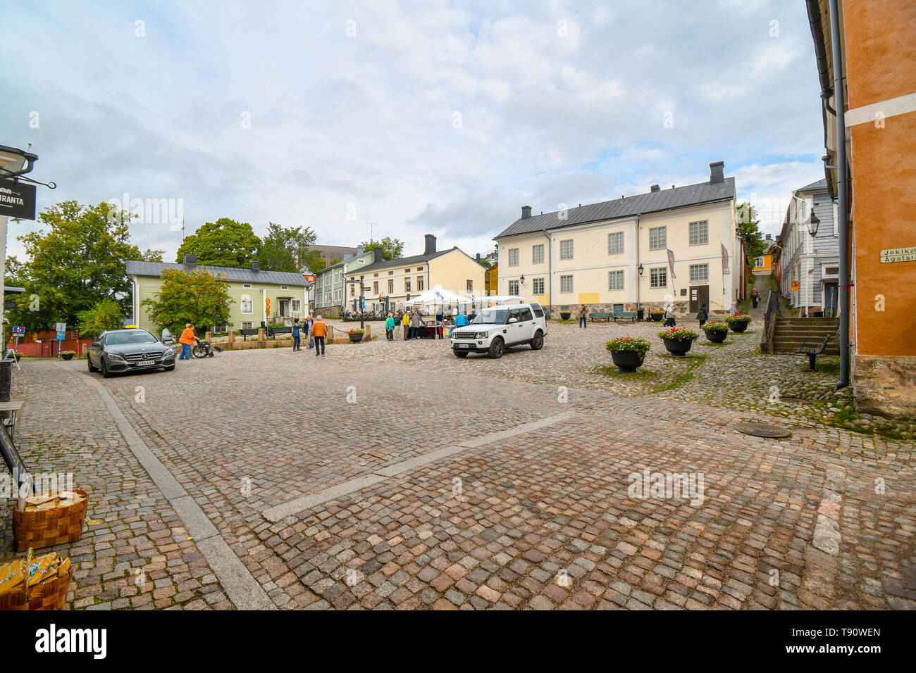 Tourists and local Finns begin to set up market stalls in the town square in front of the Porvoo Museum in the medievla village of Porvoo, Finland Stock Photo