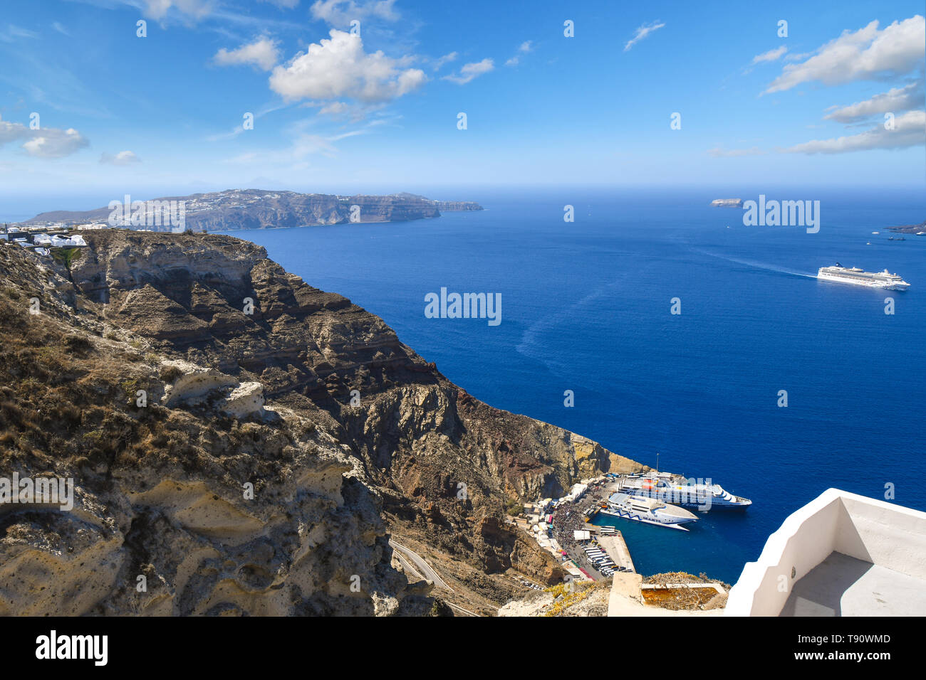 View from the hills near Oia of the cruise and boat port and ships at sea inside the caldera on the island of Santorini, Greece. Stock Photo