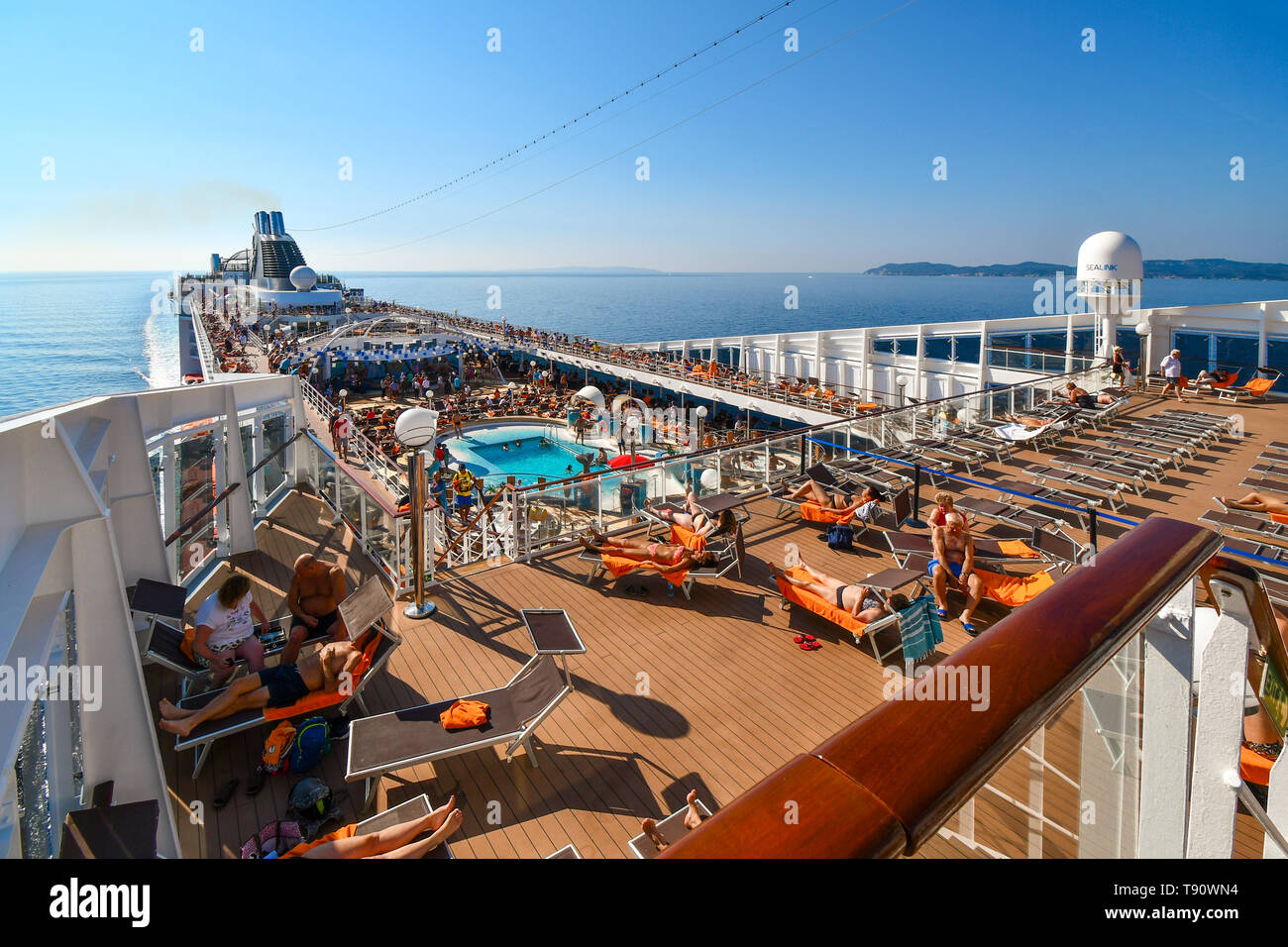 A large cruise ship with tourists on deck approaches the island of Corfu Greece on a summer day in the Ionian Sea. Stock Photo