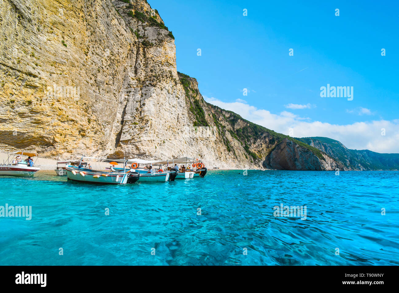 Boats line up at the shoreline in the clear waters off the sandy Paradise Beach or Chomi Beach on a sunny day in Corfu Greece. Stock Photo