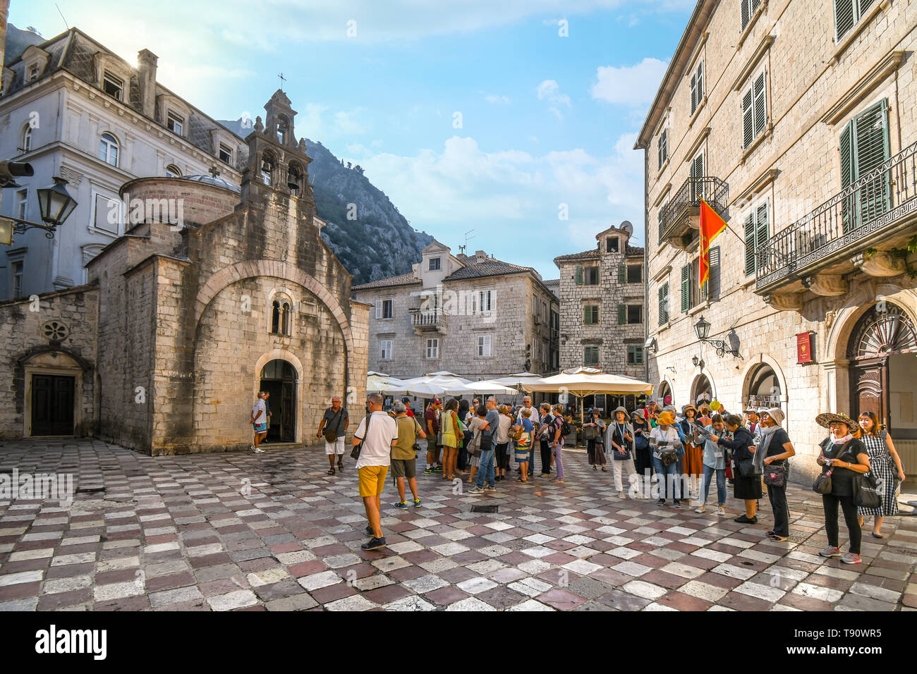 Tourists gather on St Luke's square in front of the old church with it's three bell towers in Kotor, Montenegro. Stock Photo