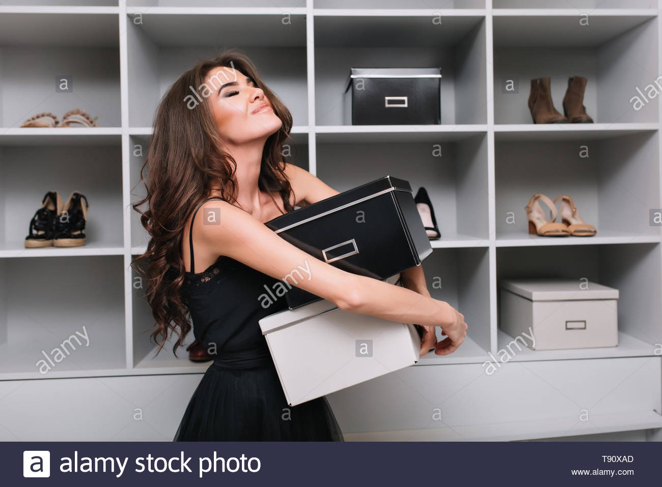 Pretty young woman hugging boxes of shoes around stylish dressing room, wardrobe. She's very happy, pleased, has closed eyes, she bought what she wanted. She wearing black dress, has long curly hair. - Stock Image