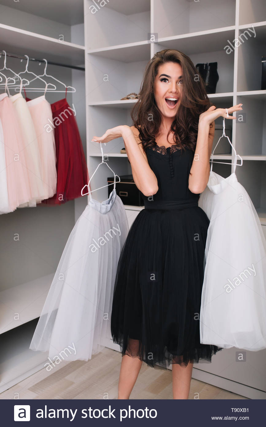 Gorgeous young woman with happy look holding beautiful white fluffy skirts in big nice wardrobe, pleasantly surprised, shocked, cheerful. Fashionable model wearing black dress, elegant look. - Stock Image