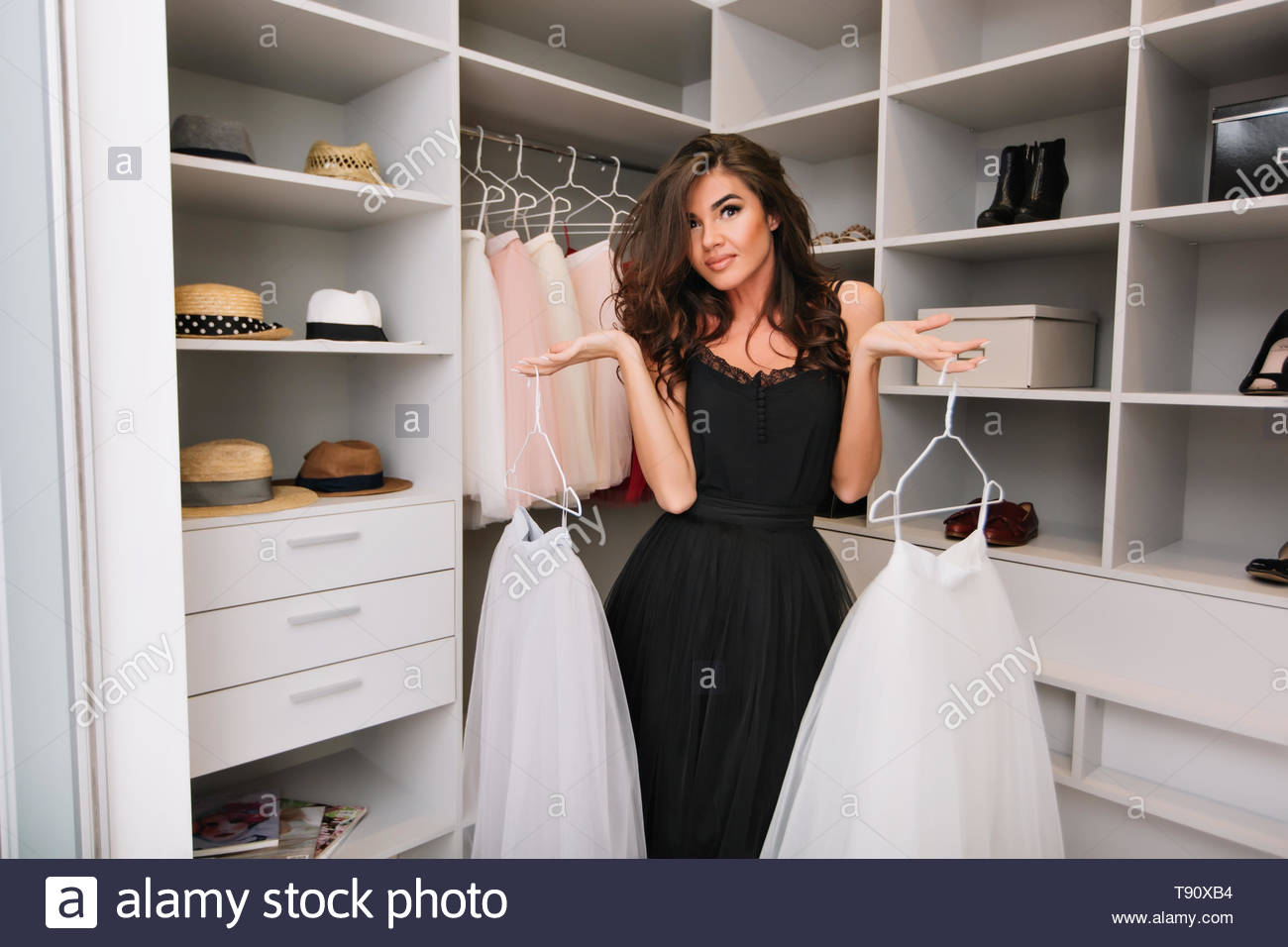Beautiful woman with brown long curly hair in nice wardrobe around clothes, hats, shoes, holding white fluffy skirts, deciding what to wear. Model with fashionable  look, wearing black elegant dress. - Stock Image