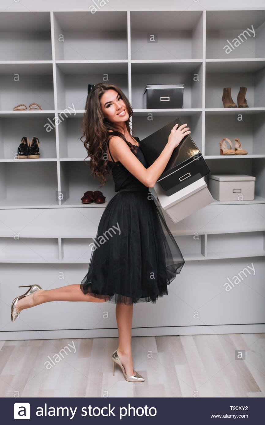 Attractive smiling girl bought new shoes, holding boxes in hands, standing in dressing room, wardrobe. She's looking to camera, one leg up. She wearing in black fluffy dress and silver high heels. - Stock Image