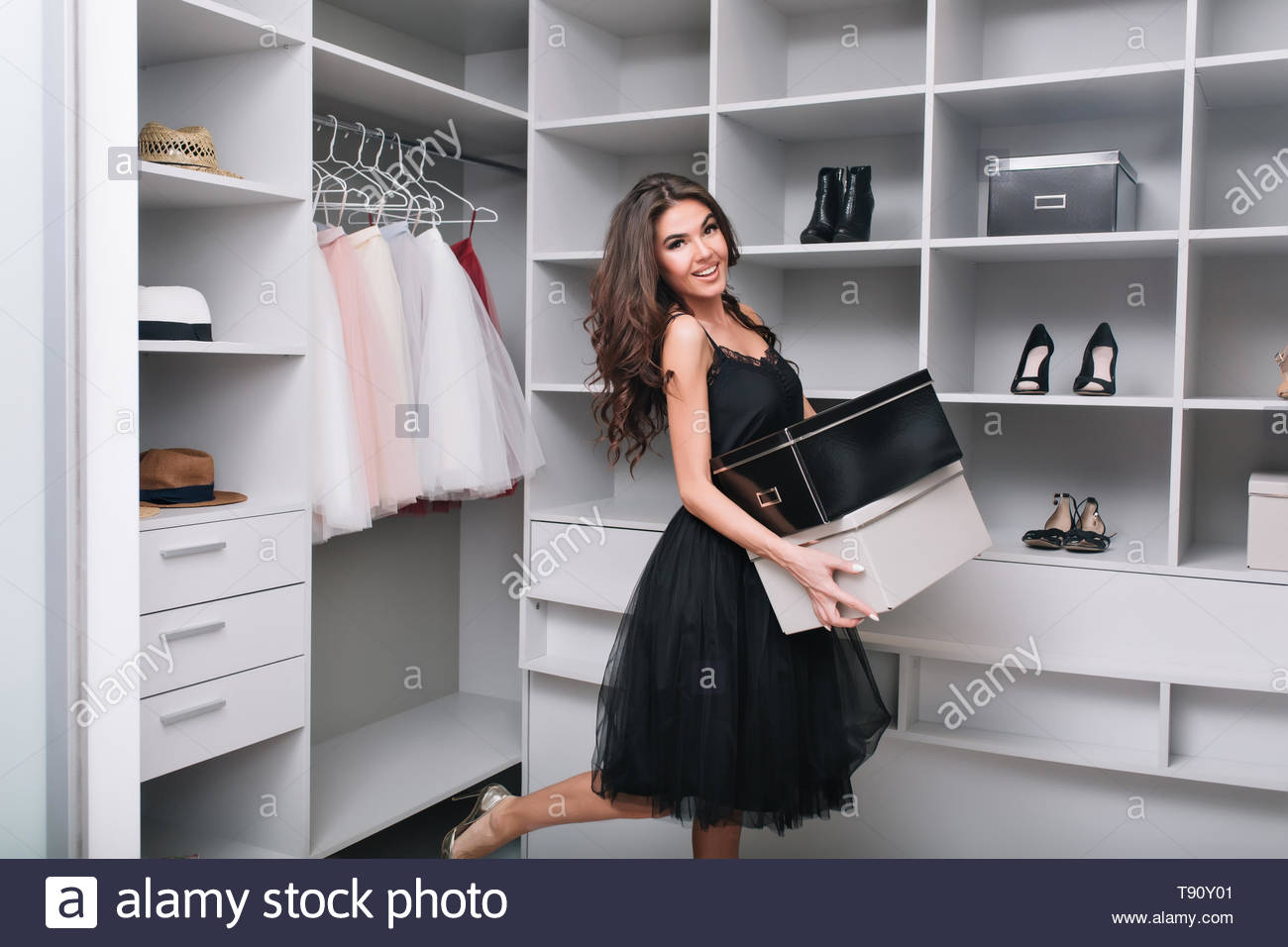 Attractive happy young woman just bought new shoes, holding boxes in hands, standing in dressing room, wardrobe. She's smiling and looking to camera. She wearing in black dress with fluffy skirt. - Stock Image