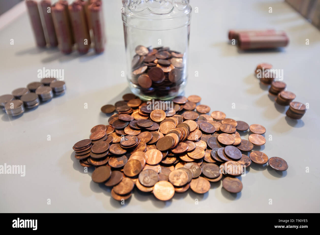 Counting pennies and coin money from spare change savings. - Stock Image