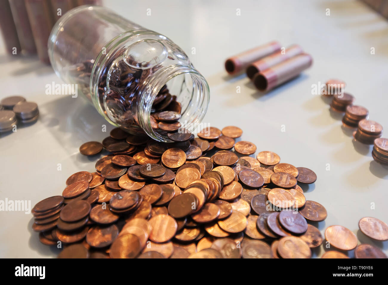 A spilled glass jar of pennies and coins from piggy bank or spare change savings. - Stock Image