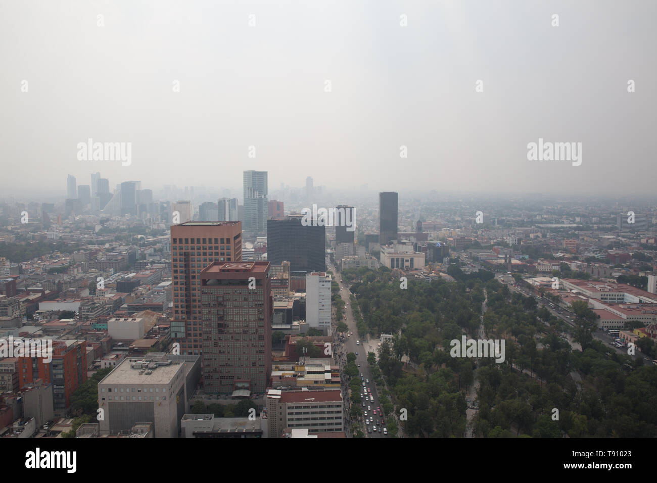 A haze of hazardous smoke covers Mexico City, Mexico on May 15, 2019. A series of wildfires on the city and its outskirts have combined with stagnant weather conditions to cloak the metropolitan area of more than 22 million people in a gray cloud of air pollution. The Environmental Commission of the Megalopolis issued an Extraordinary Environmental Contingency for the Mexico City metropolitan area after measuring extremely high levels of PM2.5 — fine particulate matter, on Tuesday. Mexico City's government has advised people to stay indoors, cancelled schools and restricted traffic due to air  Stock Photo
