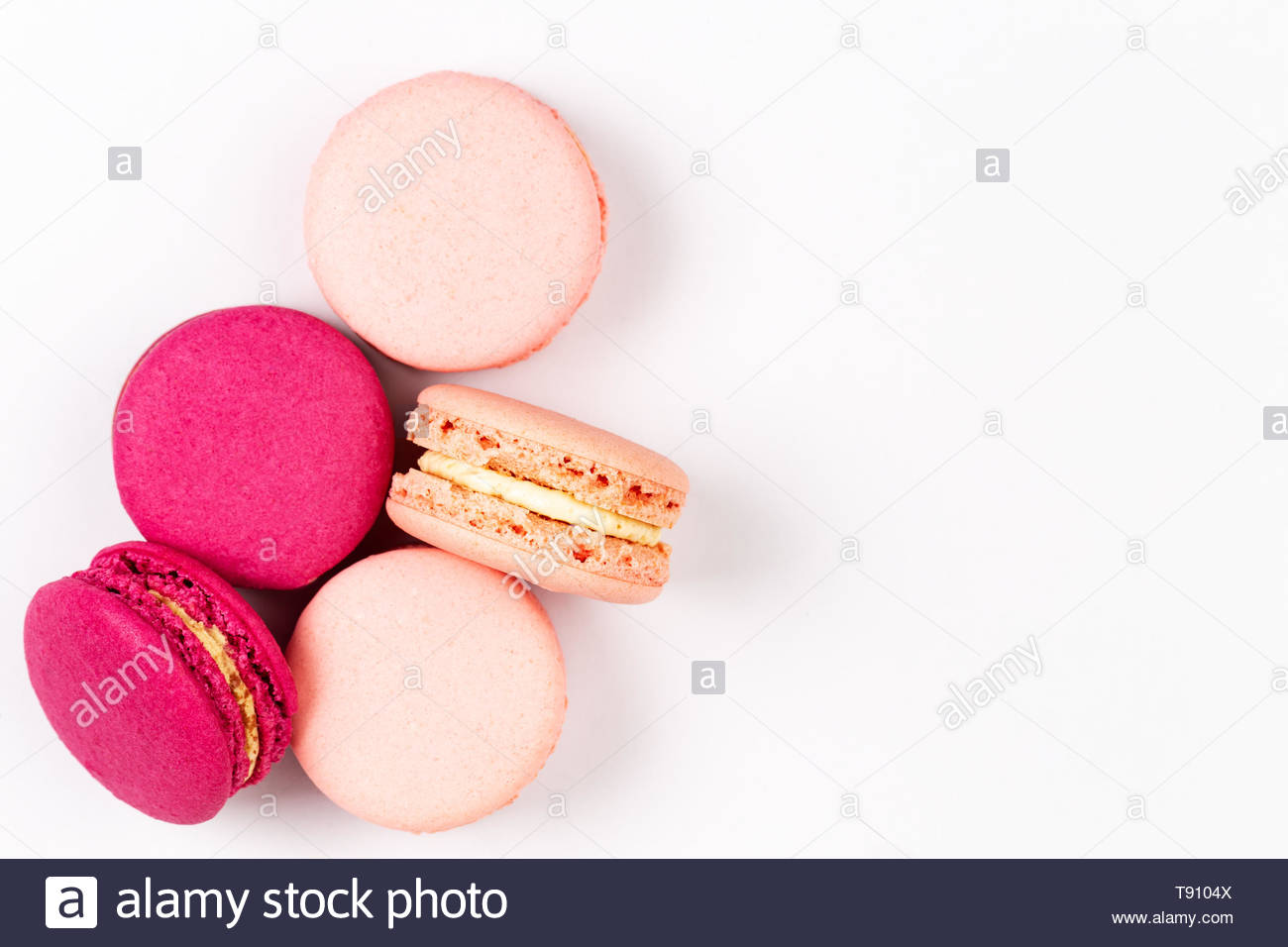 French pink and fuchsia magenta macarons or macaroons, over a white background with copyspace, top view. - Stock Image