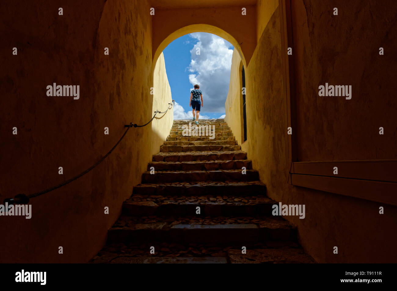 Climbing stairs out of darkness into the light at Forte de Santa Luzia, Elvas, Portugal - Stock Image