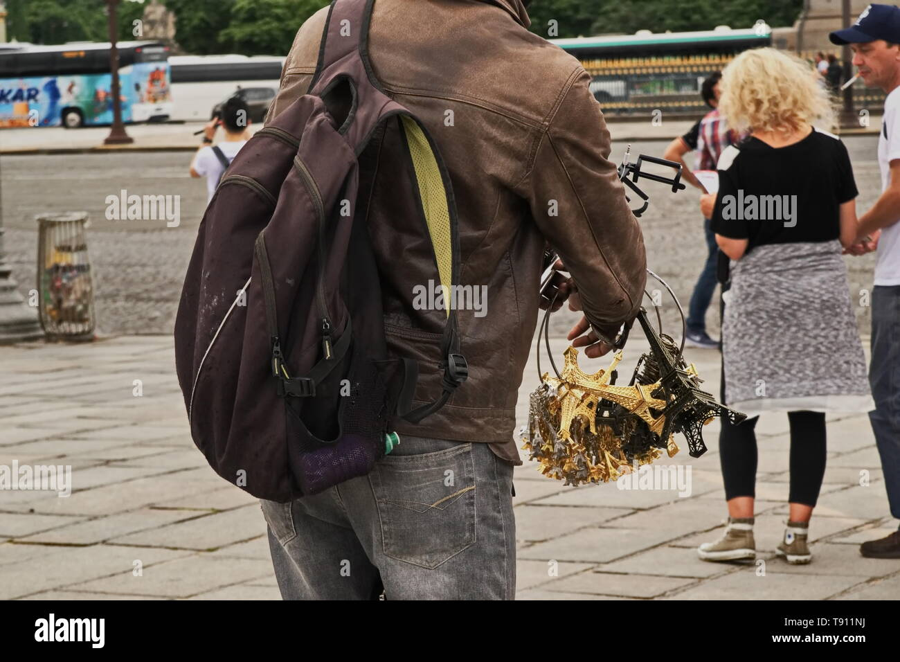 Illegal street vendor taking inventory of his merchandise while looking on at tourists Stock Photo