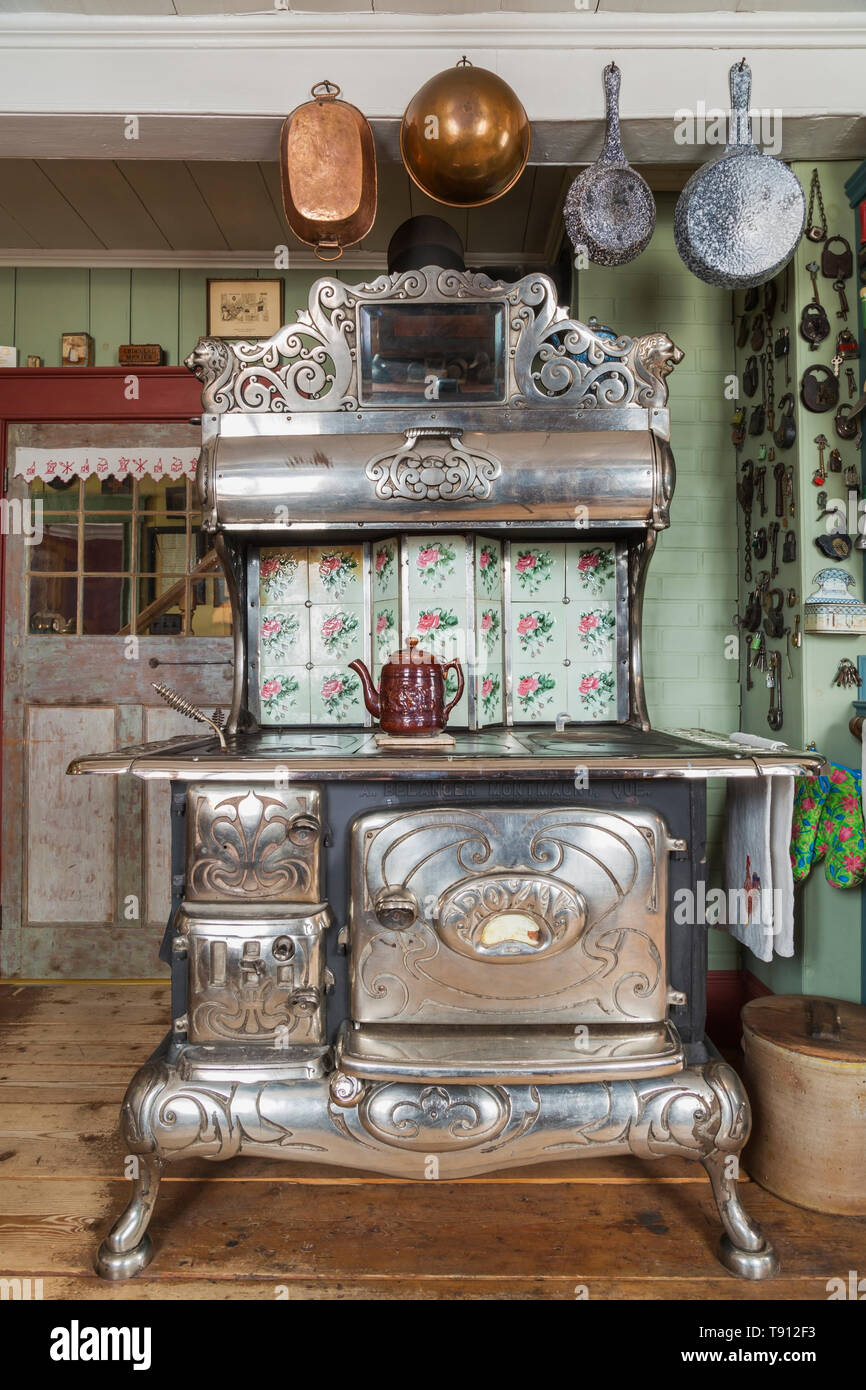 Antique 1915 Belanger Royal wood-burning cooking stove in kitchen with worn wide pinewood plank floorboards inside an old 1835 Canadiana cottage style - Stock Image