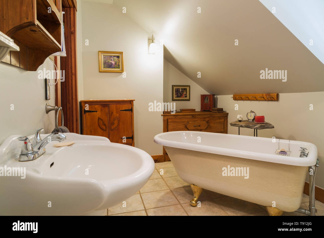 White pedestal wash sink, claw foot bathtub and antique pinewood cabinets in en suite with ceramic tiles on upstairs floor inside a 1990s contemporary - Stock Image