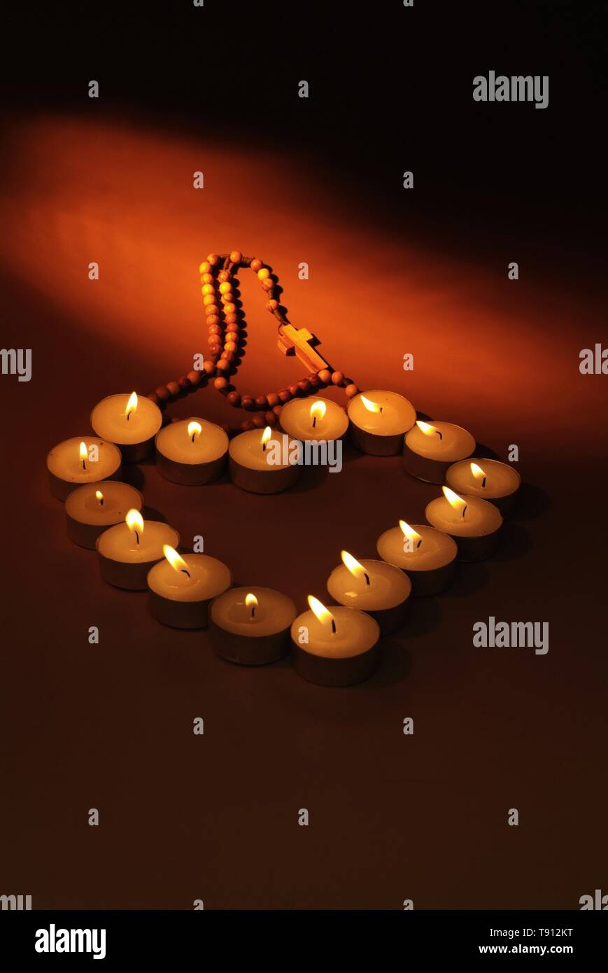Heart made of candles on a black background. Symbol of love and faith made of burning red candles isolated - Stock Image