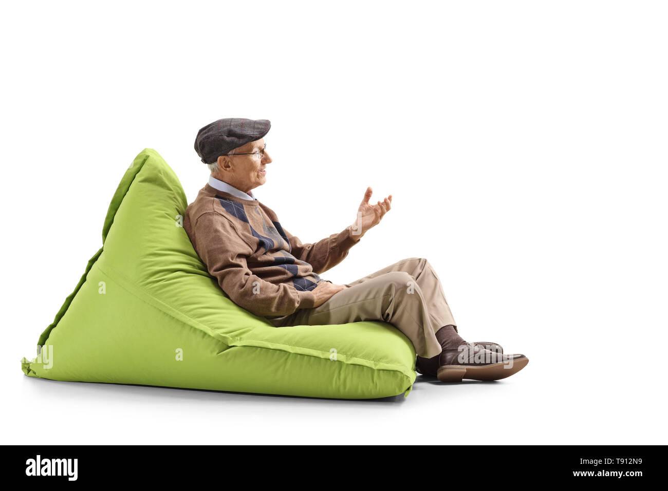 Full length profile shot of a senior man sitting on a bean bag and gesturing with hand isolated on white background - Stock Image