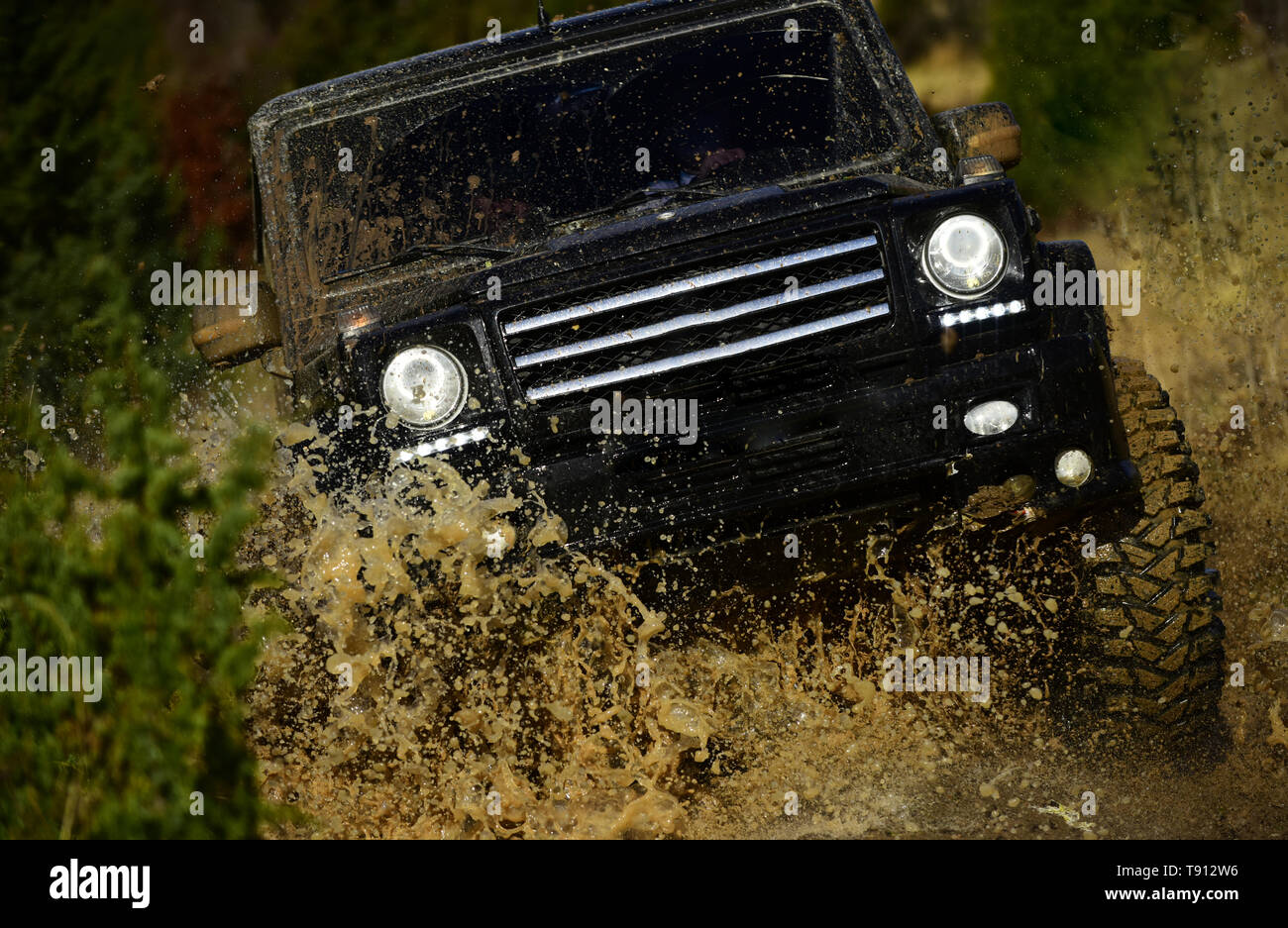 Competition, energy and motorsport concept. Off road vehicle or SUV crossing puddle with dirt splash. Car racing in autumn forest. Auto racing on fall - Stock Image