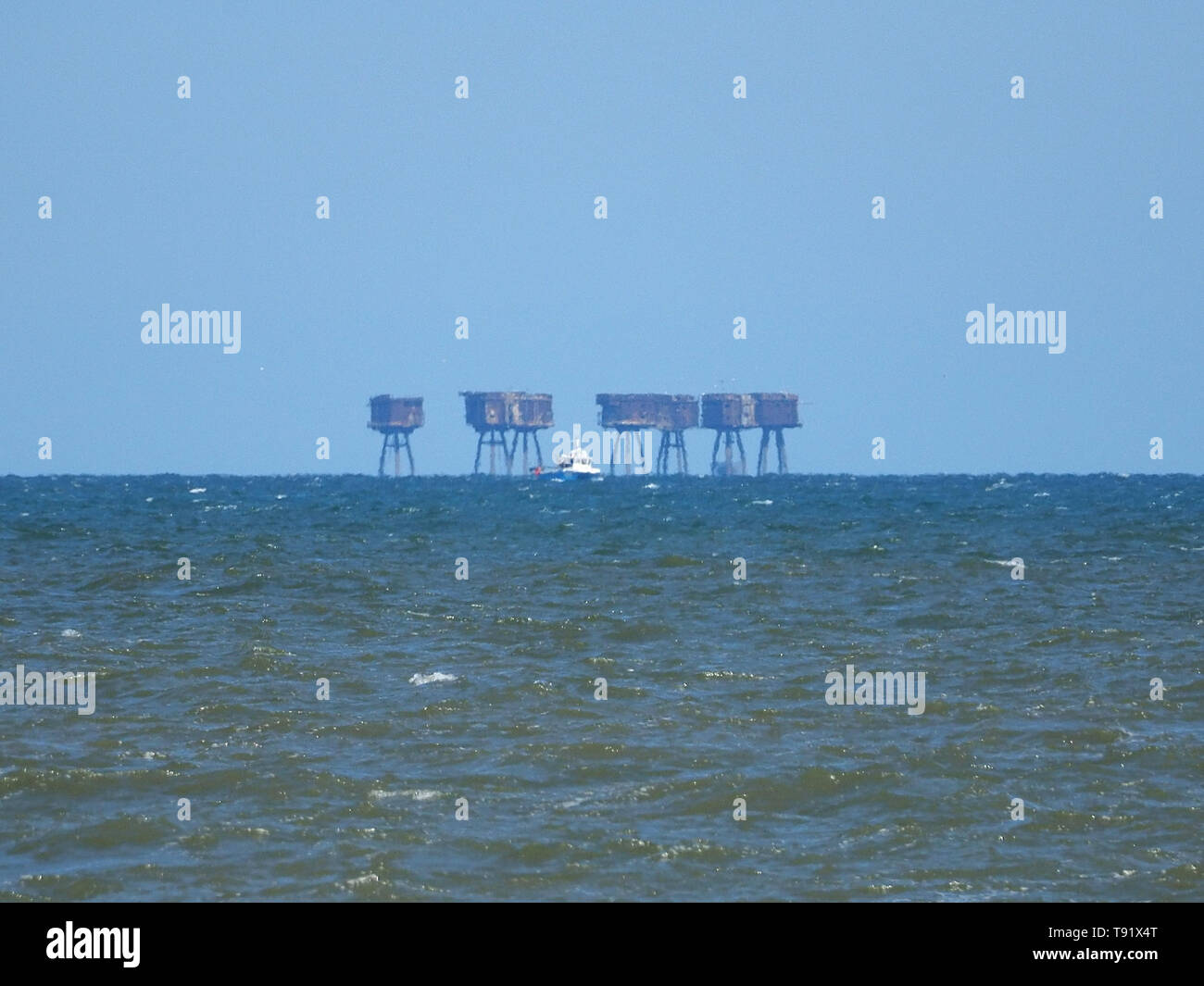 Leysdown, Kent, UK. 16th May, 2019. UK Weather: a sunny and warm afternoon in Leysdown, Kent. A fishing boat passes the Red Sands towers. Credit: James Bell/Alamy Live News - Stock Image