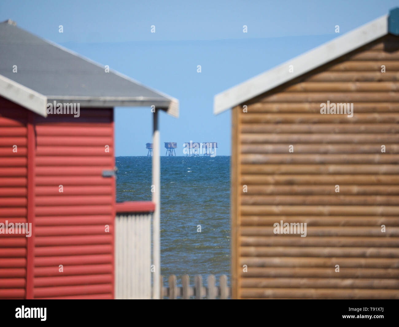 Leysdown, Kent, UK. 16th May, 2019. UK Weather: a sunny and warm afternoon in Leysdown, Kent. The Red Sands towers as seen through a gap in beach huts. Credit: James Bell/Alamy Live News - Stock Image
