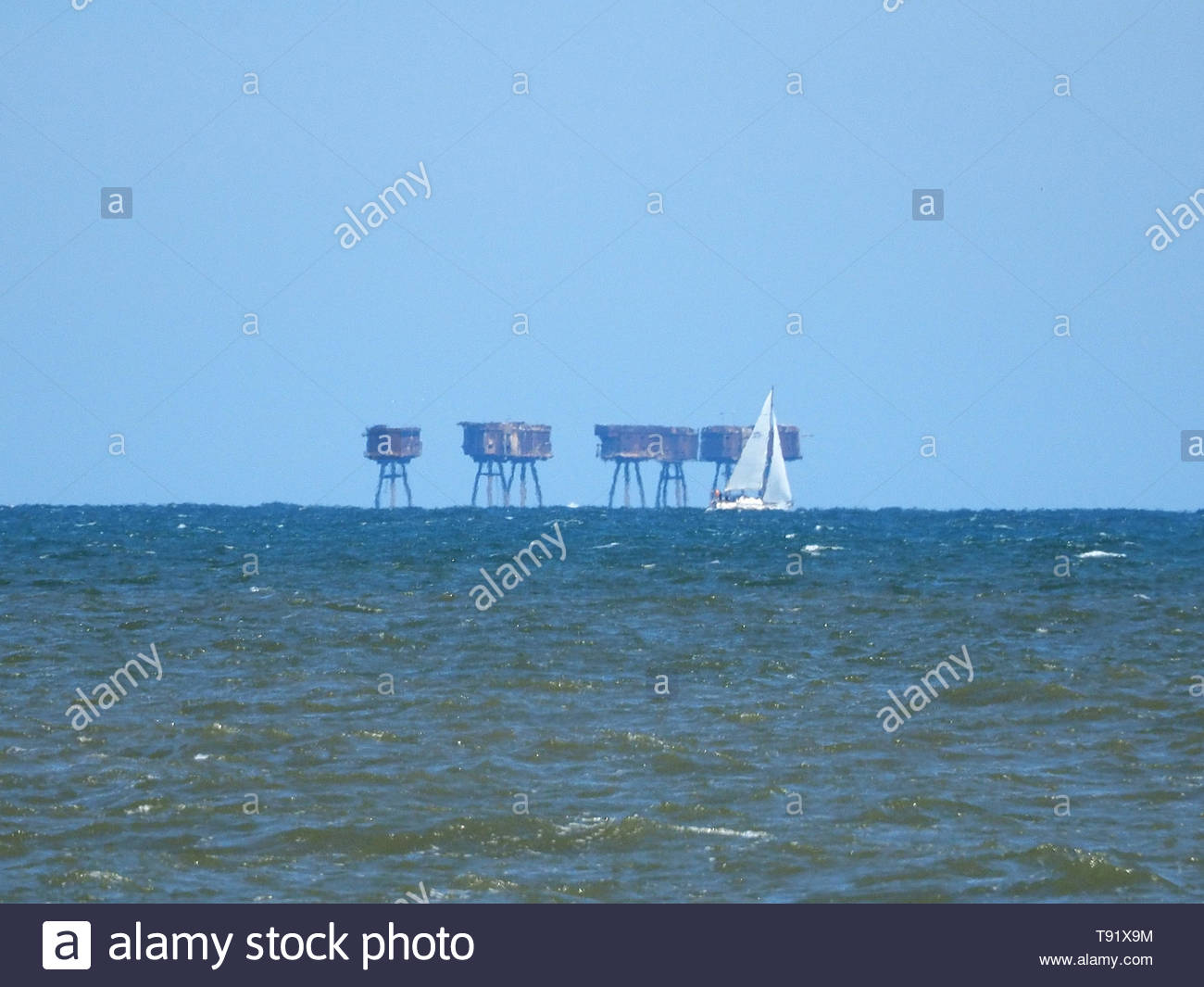 Leysdown, Kent, UK. 16th May, 2019. UK Weather: a sunny and warm afternoon in Leysdown, Kent. A sailing yacht sails past the Red Sands towers which are around 5 miles offshore. Credit: James Bell/Alamy Live News - Stock Image