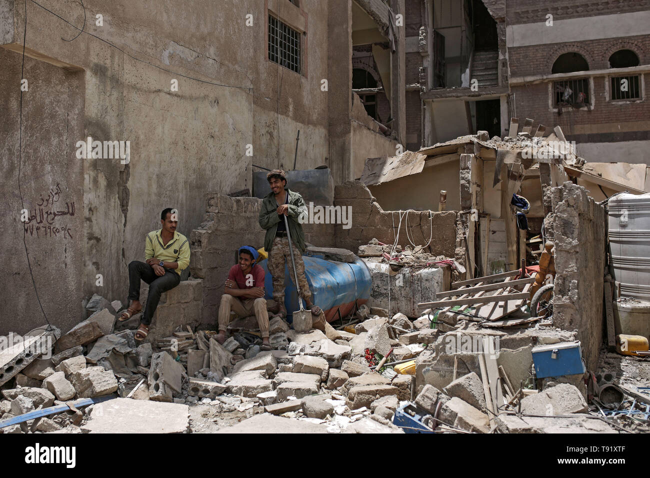 Sanaa, Yemen. 16th May, 2019. Yemenis inspect the site of a Saudi-led coalition airstrike. According to a local health official linked to the Houthi rebels the airstrike killed at least six Civilians. The coalition carried out several airstrikes on the Houthi-held capital Sanaa on Thursday, after the Iranian-aligned movement claimed responsibility for drone attacks on Saudi oil installations. Credit: Hani Al-Ansi/dpa/Alamy Live News - Stock Image