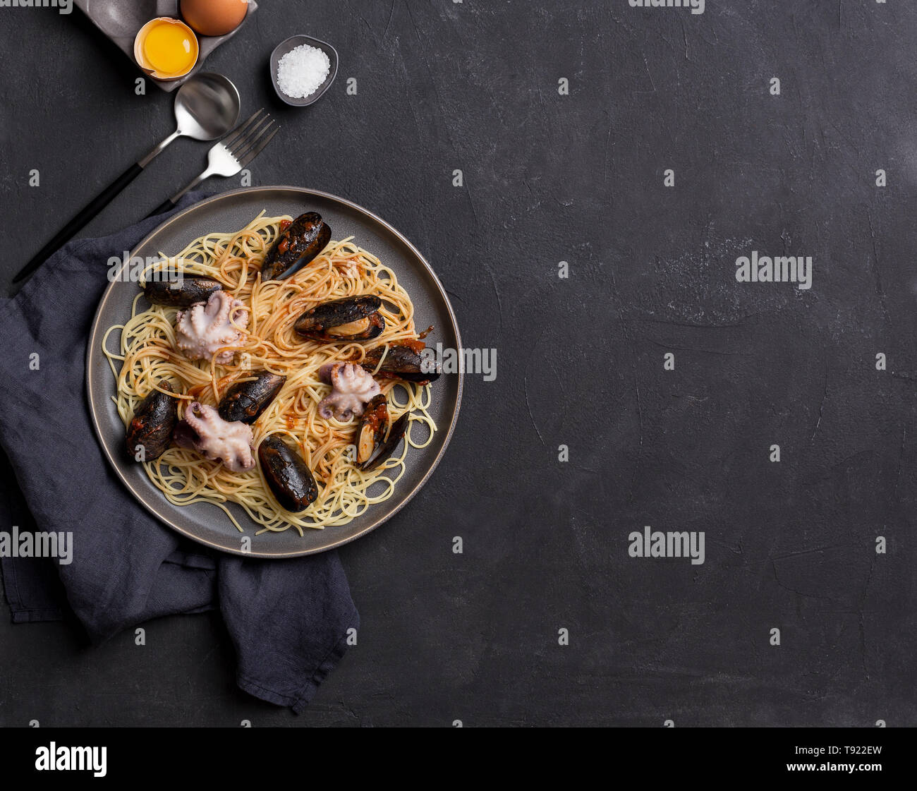 Copy space for text. Mediterranean pasta with octopus, mussels and tomatoes souse in plate. Free space for text, background for banner - Stock Image