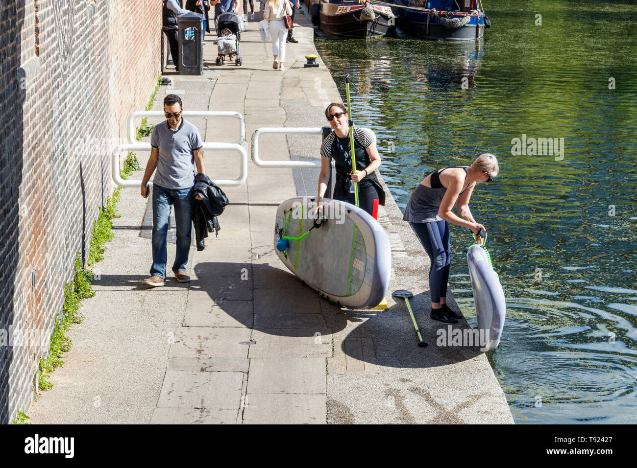 Two female paddleboarders exiting Regent's Canal onto the towpath at St Pancras Lock, King's Cross, London, UK - Stock Image