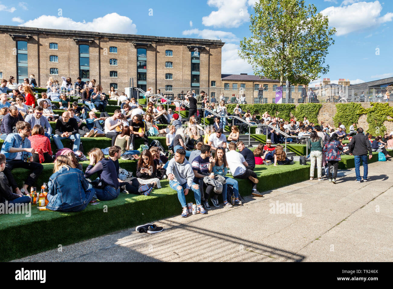 Londoners basking in spring sunshine on the steps of Granary Square by Regent's Canal, King's Cross, London, UK, 2019 - Stock Image