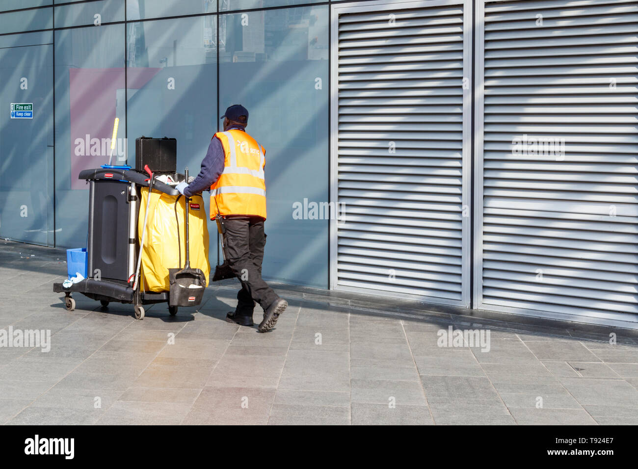 A male street cleaner pushing a cleaning trolley in the redeveloped area of King's Cross, London, UK Stock Photo