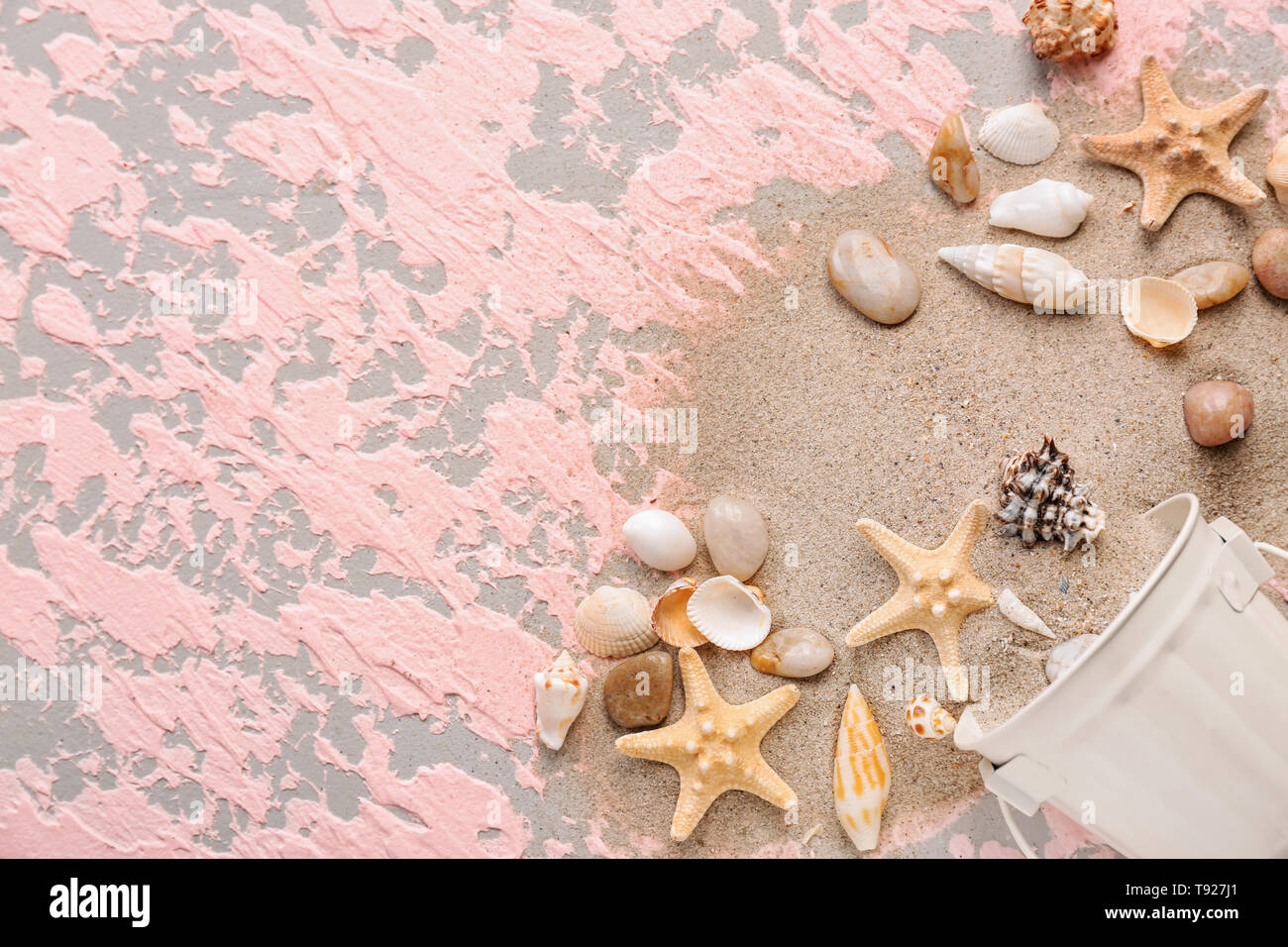 Overturned bucket with with different sea shells and sand on color background - Stock Image