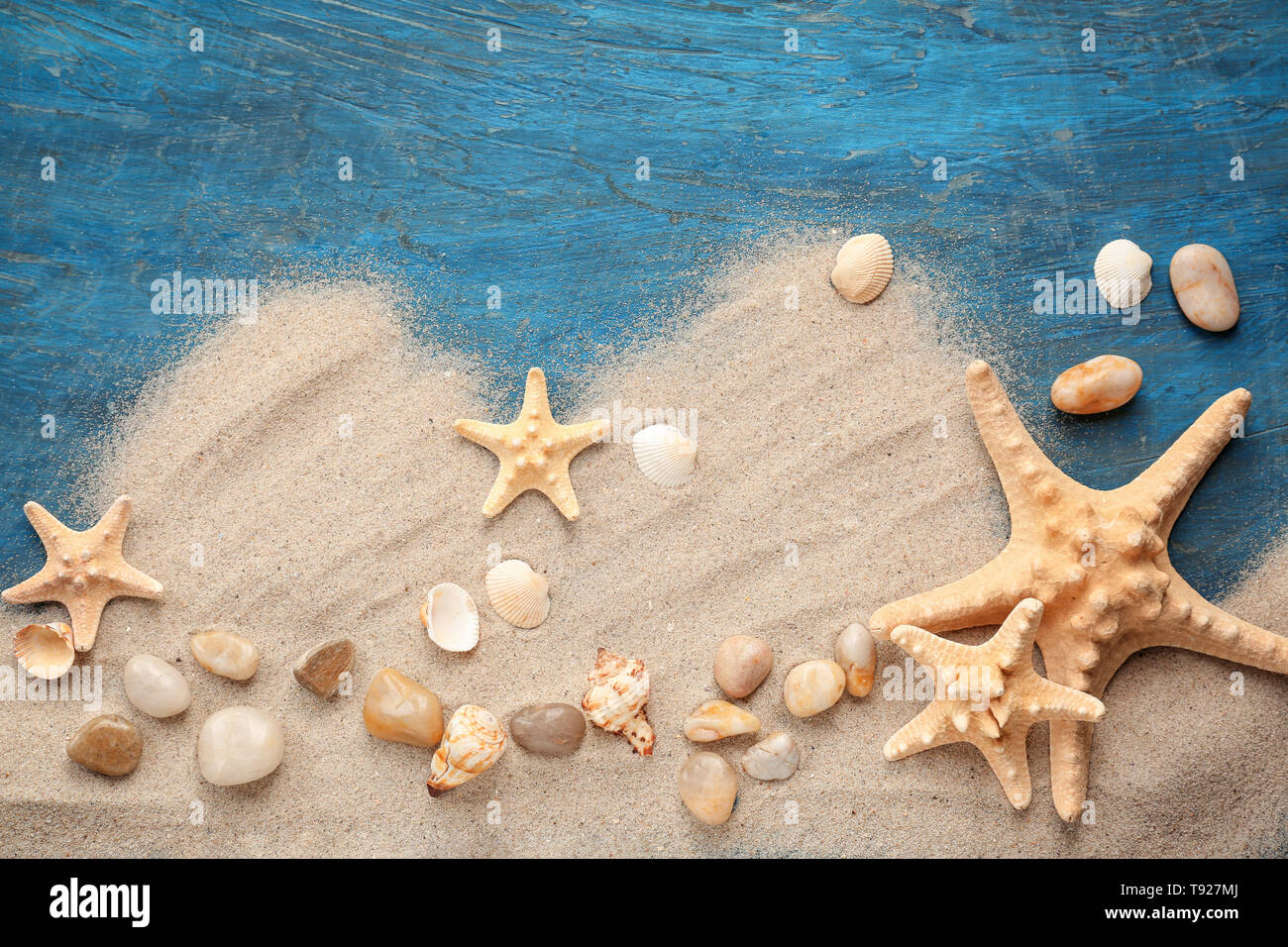 Composition with different sea shells and sand on color background - Stock Image