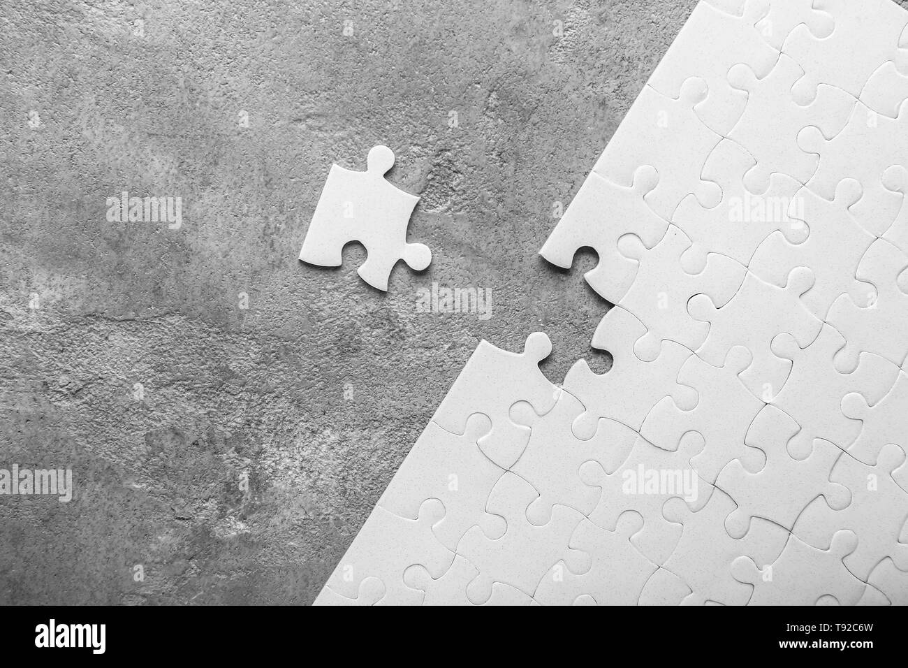 White jigsaw puzzle with piece on grey background - Stock Image