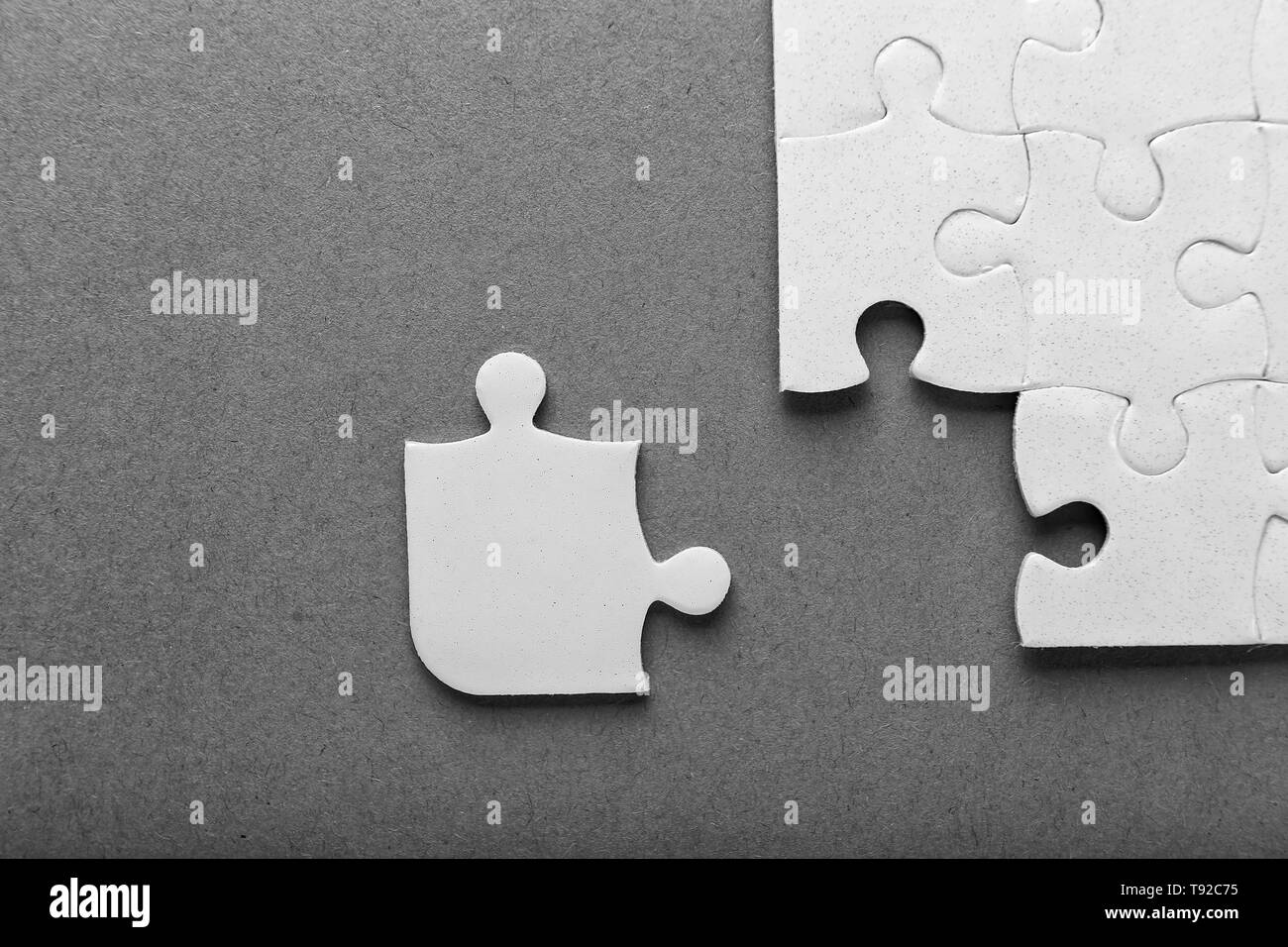 Incomplete jigsaw puzzle on grey background - Stock Image