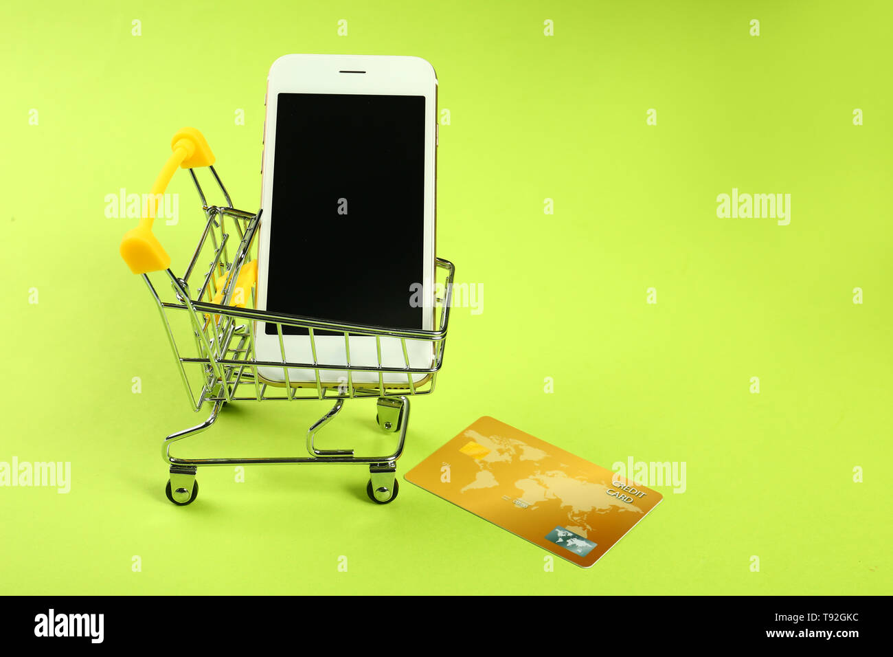98424c1033b Small cart with mobile phone and credit card on color background. Online  shopping concept -