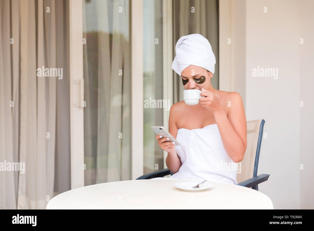 Happy smiling woman in under-eye patches readind sms message and drinking coffee at hotel terrace resort. morning holiday concept. Good news. Stock Photo