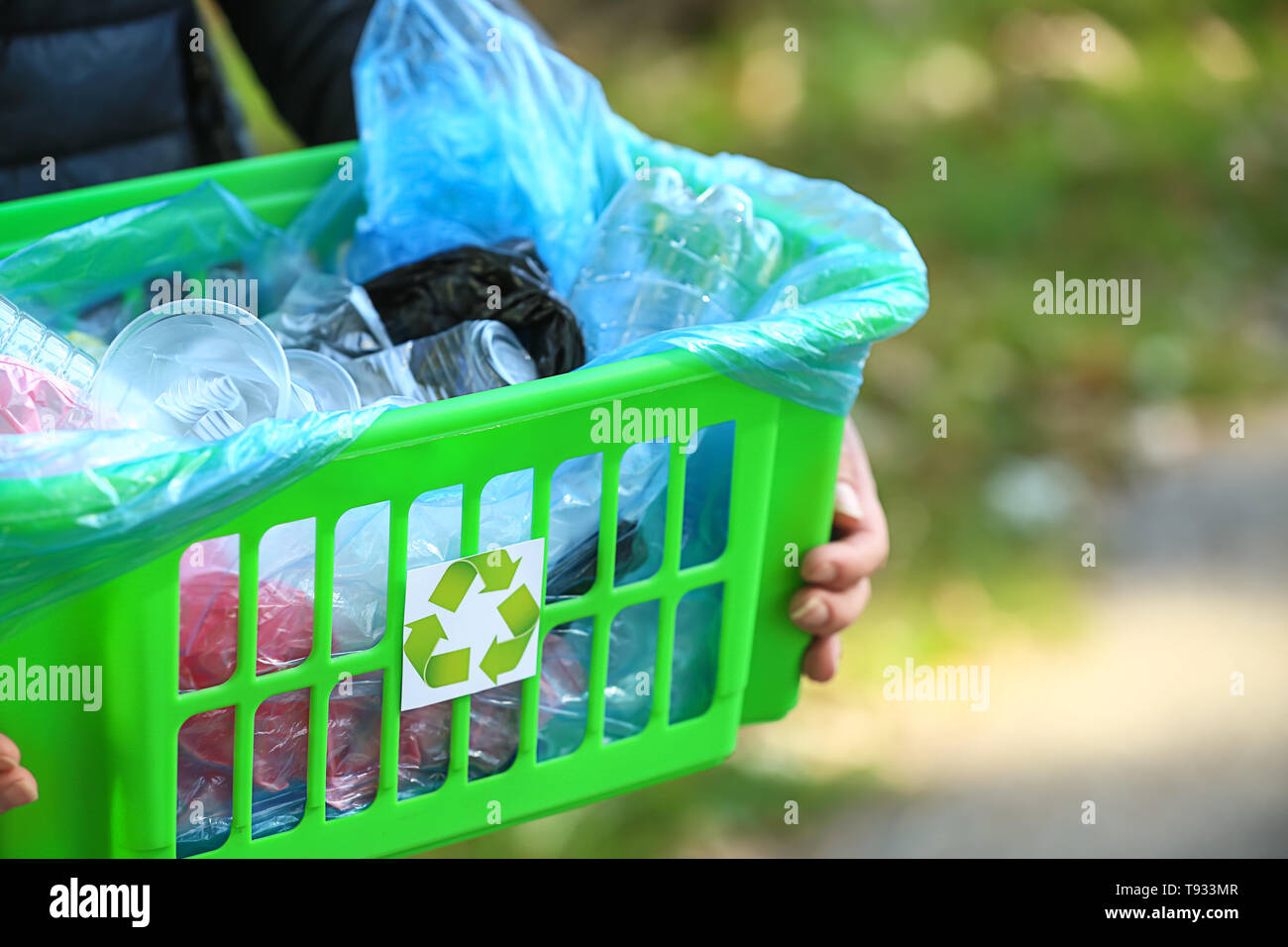 Woman holding box with trash outdoors - Stock Image