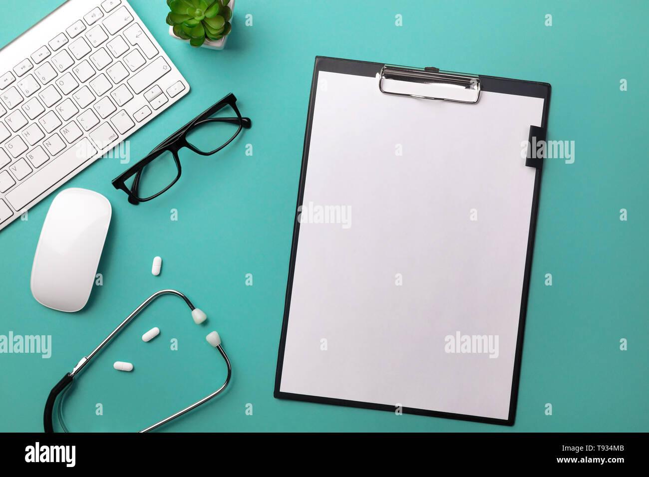 Stethoscope in doctors desk with tablet, pen, keyboard