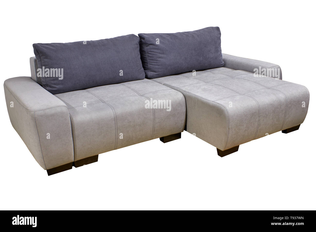 modern stylish corner sofa in white fabric with gray pillows - Stock Image