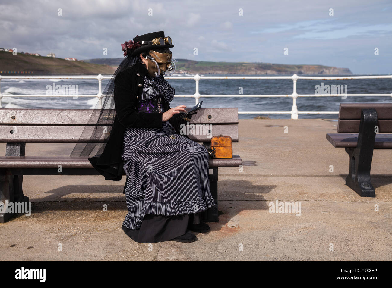 A Goth / Steampunk woman checks her phone during a break in the Goth Weekend celebrations at Whitby,North Yorkshire,England,UK - Stock Image
