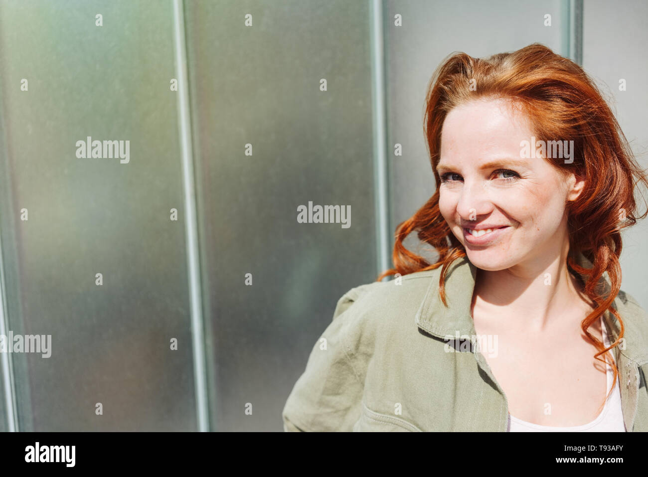 Cheeky happy young redhead woman with tousled long hair grinning at camera in front of an urban building with copy space - Stock Image