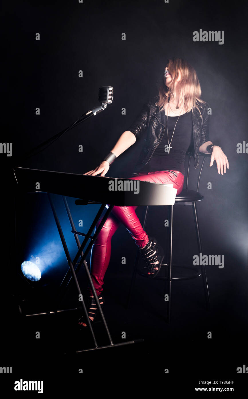 Blonde girl musician pianist plays perform on white digital piano, sits on chair, sings into retro microphone. Woman teacher shows how to play music - Stock Image