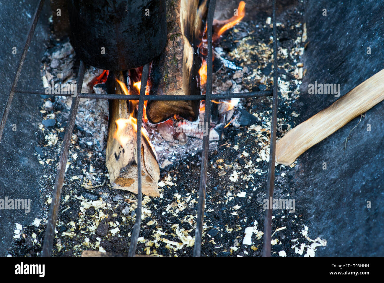 Cooking in sooty cauldron on campfire at forest - Stock Image